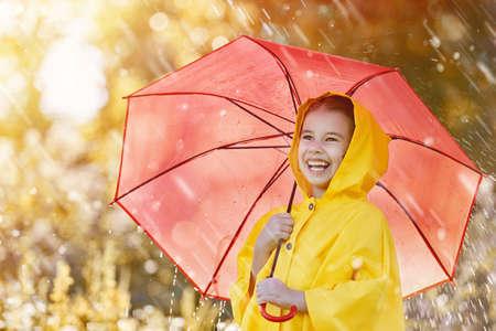 가을 샤워 아래에 빨간색 우산 행복한 재미있는 자식. 소녀 노란색 비옷을 착용 하 고 강우량을 즐기고있다. 야외에서 자연을 노는 아이. 가족 공원에서 산책.