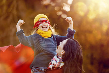 super woman: Happy family on autumn walk! Mother and daughter walking in the Park and enjoying the beautiful autumn nature. Child girl plays superhero. Stock Photo