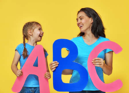 Happy smiling child and teacher are having big letters. Yellow, blue and pink colors. photo