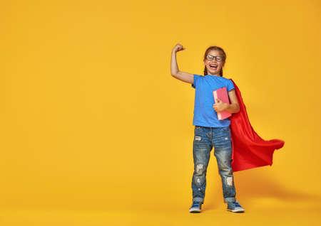 小さな子供は、スーパー ヒーローを果たしています。明るい色の壁の背景を子供します。教育と成功のコンセプトです。黄色、赤、青。