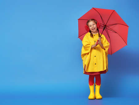 Happy funny child with red umbrella posing on blue wall background. Girl is wearing yellow raincoat and rubber boots. photo
