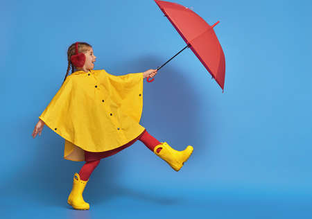 Happy funny child with red umbrella posing on blue wall background. Girl is wearing yellow raincoat and rubber boots.