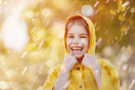 Happy funny child under the autumn shower. Girl is wearing yellow raincoat and enjoying rainfall.  photo