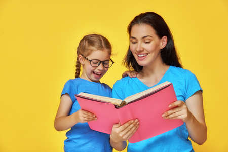 Back to school! Happy cute industrious child and her mother are reading the book indoors. Kid and adult on background of bright wall. Yellow, pink and blue color. photo