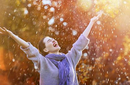 秋のシャワーの下で幸せな美しい若い女性。女の子は、降雨を楽しんでいます。