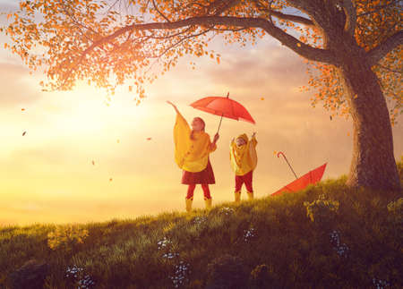 Two happy funny children under the autumn shower. Girls are wearing yellow raincoats and enjoying rainfall. Sisters playing together on the nature outdoors. Family walk in the park. photo