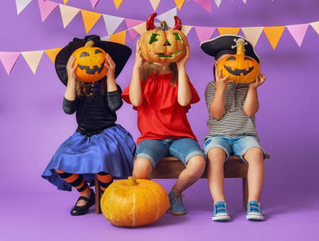 Happy brother and two sisters at Halloween. Funny kids in carnival costumes on background of purple wall. Cheerful children and pumpkins. Stock Photo