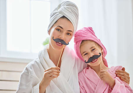 Funny family! Mother and her child with a paper accessories. Mom and daughter preparing for a party and having fun. Beautiful young woman and cute girl with mustache on sticks.