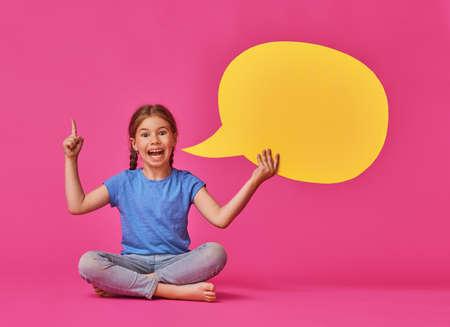 Mignonne petite fille enfant avec discours de dessin animé sur fond coloré. Couleurs jaunes, roses et bleus. Banque d'images - 84289459