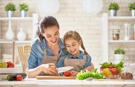 La comida sana en casa. Familia feliz en la cocina. Madre e hija hijo están preparando las verduras y frutas. Foto de archivo - 84289468