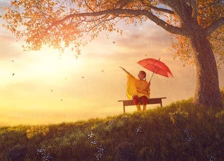 秋のシャワーの下で赤い傘と幸せな面白い子。女の子は黄色のレインコートを着て、雨を楽しんでします。自然で遊ぶ子供。家族は公園を歩きます