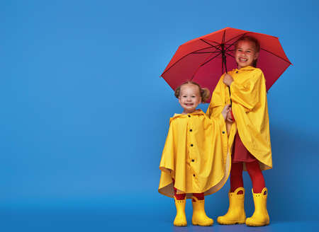 Two happy funny children with red umbrella posing on blue wall background. Girls is wearing yellow raincoat and rubber boots. photo