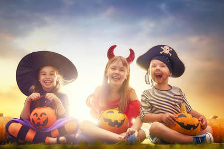 Happy brother and two sisters at Halloween. Funny kids in carnival costumes outdoors. Cheerful children and pumpkins on sunset background.