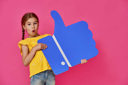 Cute little child girl with cartoon like icon on colorful background. Yellow, pink and blue colors.