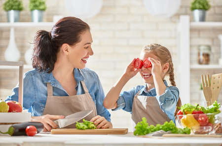 Healthy food at home. Happy family in the kitchen. Mother and child daughter are preparing the vegetables and fruit. photo