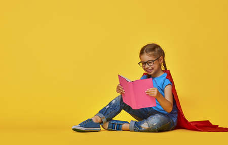 Little child plays superhero. Kid on the background of bright color wall. Education and success concept. Yellow, red and  blue. photo