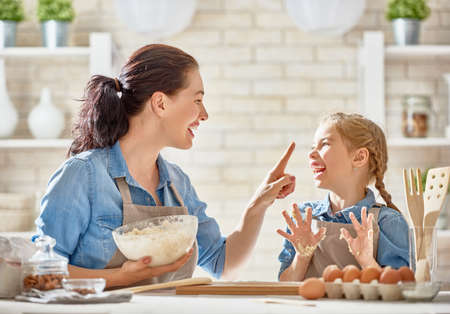 Happy loving family are preparing bakery together. Mother and child daughter girl are cooking cookies and having fun in the kitchen. Homemade food and little helper. photo