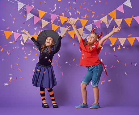 Twee gelukkige zussen op Halloween. Grappige kinderen in carnaval kostuums op de achtergrond van paarse muur. Vrolijke kinderen zijn confetti.