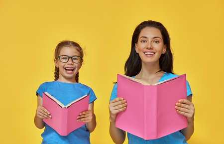 Back to school! Happy cute industrious child and her mother are reading the books indoors. Kid and adult on background of bright wall. Yellow, pink and blue color. photo