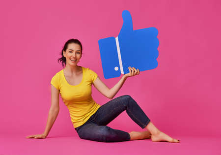Beautiful young woman girl with cartoon like icon on colorful background. Yellow, pink and blue colors. Stock Photo
