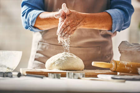 Close up view of baker is working. Homemade bread. Hands preparing dough on wooden table.