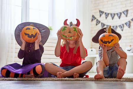 Feliz hermano y dos hermanas en Halloween. Niños divertidos en trajes de carnaval en el interior. Los niños alegres juegan con calabazas y dulces.