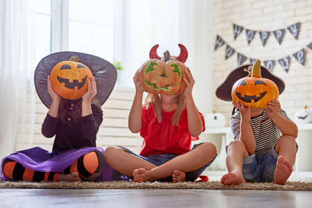 Happy brother and two sisters on Halloween. Funny kids in carnival costumes indoors. Cheerful children play with pumpkins and candy. Standard-Bild