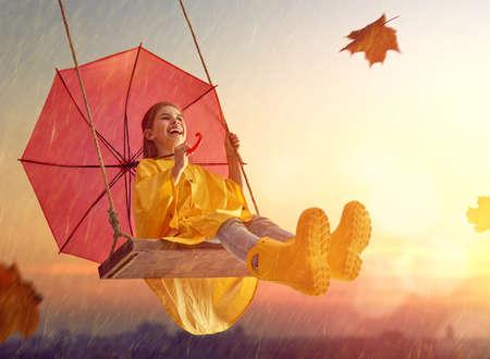Gelukkig grappig kind met rode paraplu tijdens de herfst douche. Meisje draagt ??gele regenjas, rubberen laarzen en geniet van regenval. Kid spelen op de natuur buiten. Familie wandeling in het park.