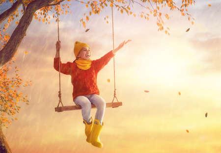 秋のシャワーの下で幸せな面白い子供。女の子は黄色いゴム長靴を履いて、雨を楽しんでいます。 写真素材