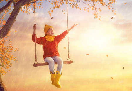 Happy funny child under the autumn shower. Girl is wearing yellow rubber boots and enjoying rainfall. 版權商用圖片 - 85069381