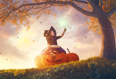 Fröhliches Halloween! Nette freundliche kleine Hexe mit einem magischen Stab und einem Buch der Zaubersprüche. Schönes Kindermädchen im Kostüm, das auf dem großen Kürbis sitzt, beschwört und lacht.