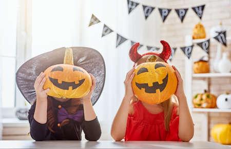 南瓜とかわいい小さな子供女の子。幸せな家族は、ハロウィンの準備します。自宅で面白い子供たち。