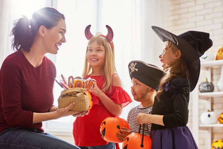 Happy family celebrating Halloween! Young mom treats children with candy. Funny kids in carnival costumes. Stock Photo