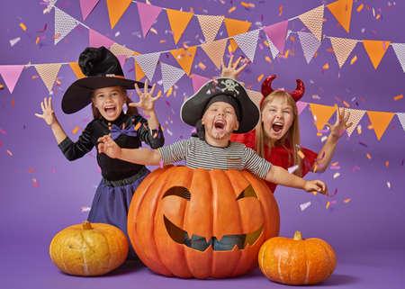 행복 한 형제와 두 자매 할로윈입니다. 보라색 벽의 배경에 카니발 의상에서 재미있는 아이. 명랑 한 아이들과 색종이와 호박.