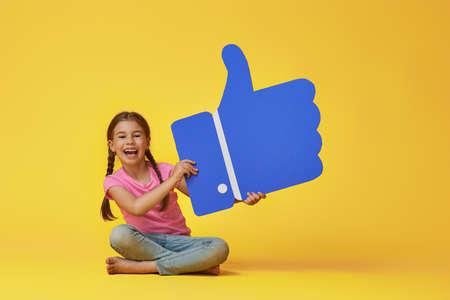Schattig klein kindmeisje met cartoon pictogram op kleurrijke achtergrond. Gele, roze en blauwe kleuren. Stockfoto