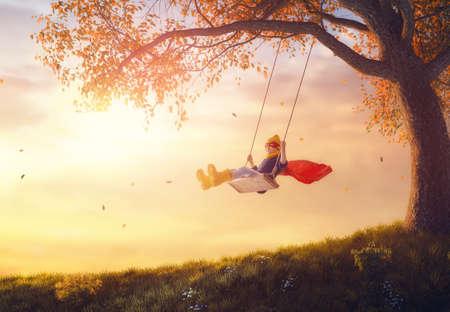 Glückliches Kind auf Schaukel im Sonnenuntergang fallen. Kleine Kinder spielen im Herbst auf dem Naturspaziergang. Mädchen im Superheld Kostüm. Standard-Bild - 85131492