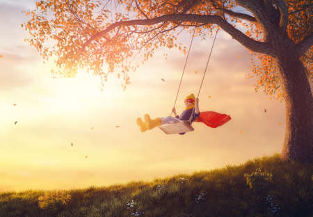 Happy child on swing in sunset fall. Little kid playing in the autumn on the nature walk. Girl in superhero costume.