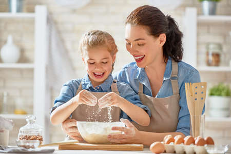 Happy loving family are preparing bakery together. Mother and child daughter girl are cooking cookies and having fun in the kitchen. Homemade food and little helper.
