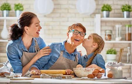 Gelukkige liefdevolle familie bereiden de bakkerij samen. Oma, mama en kind dochtermeisje koken koekjes en plezier in de keuken. Zelfgemaakt eten en kleine helper.