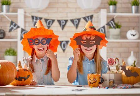 Cute little children girls with carving pumpkins, paper bats and sweets. Happy family preparing for Halloween. Funny kids at home.