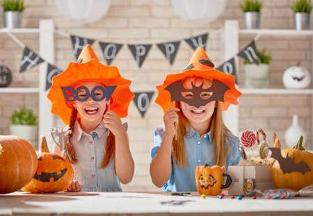 彫刻カボチャとかわいい子供たち女の子紙のコウモリとお菓子。幸せな家族は、ハロウィンの準備します。自宅で面白い子供たち。