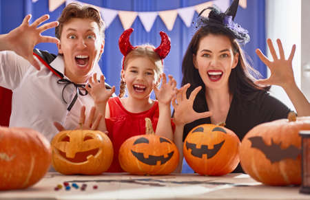 Mãe, pai e filha se divertindo em casa. Família feliz, preparando-se para o Halloween. Pessoas vestindo fantasias de carnaval.