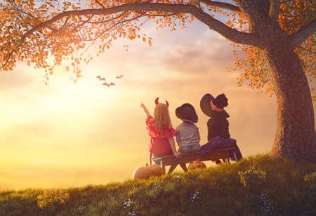 Gelukkige broer en twee zussen in Halloween. Grappige kinderen in carnavalskleding buiten. Vrolijke kinderen en pompoenen op zonsondergang achtergrond. Stockfoto