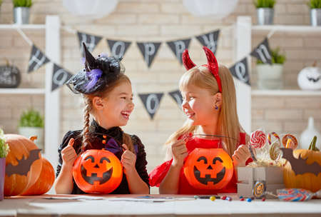Cute little children girls with carving pumpkin. Happy family preparing for Halloween. Funny kids at home.