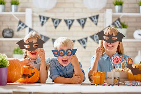Lindos niños pequeños con talla de calabaza. Familia feliz preparándose para Halloween. Niños graciosos en casa. Foto de archivo