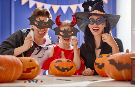 Mother, father and their daughter having fun at home. Happy family preparing for Halloween. People wearing carnival costumes. Stock Photo