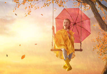 Happy funny child with red umbrella under the autumn shower. Girl is wearing yellow raincoat, rubber boots and enjoying rainfall. Kid playing on the nature outdoors. Family walk in the park.