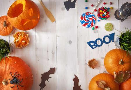 楽しいハロウィンをお過ごし下さい!家のテーブルの上にカボチャ、キャンディー、紙バットを彫刻。休日のための準備。