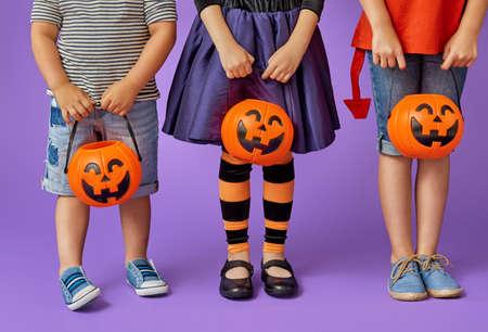 Glücklicher Bruder und zwei Schwestern bei Halloween. Lustige Kinder in Karneval Kostüme auf Hintergrund der lila Wand. Fröhliche Kinder und Kürbisse.