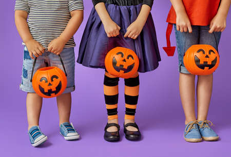 Happy brother and two sisters at Halloween. Funny kids in carnival costumes on background of purple wall. Cheerful children and pumpkins. Standard-Bild